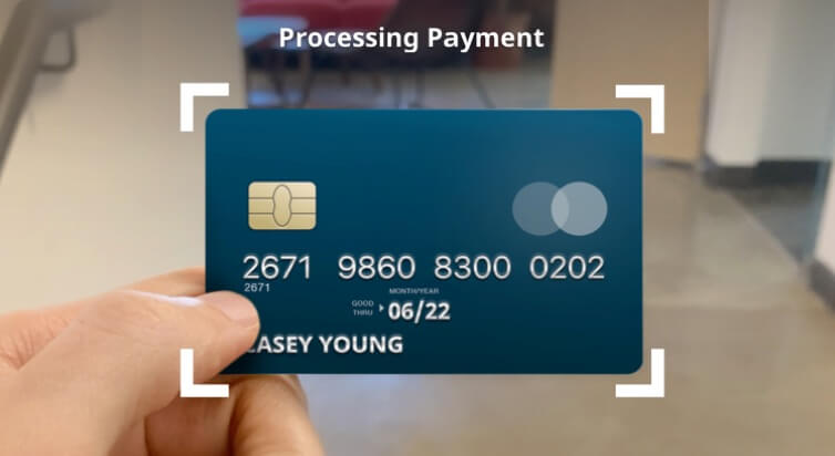 A credit card held up with the text, Processing Payment above it.